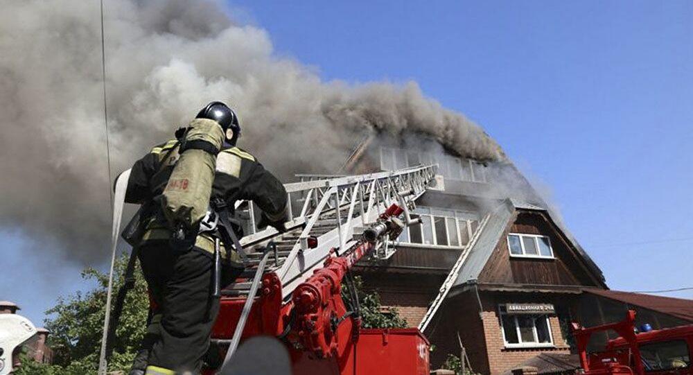 رجال إطفاء الحريق خلال إطفاء نيران اشتعلت في بيت للعجزة في قرية جيمتشوجينا في كراسنويارسك
