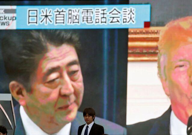 رجل يمشي قرب شاشة رصد تظهر رئيس الوزراء الياباني شينزو آبي والرئيس الأمريكي دونالد ترامب في تقرير إخباري عن اتصال هاتفي حول تهديد كوريا الشمالية، في طوكيو