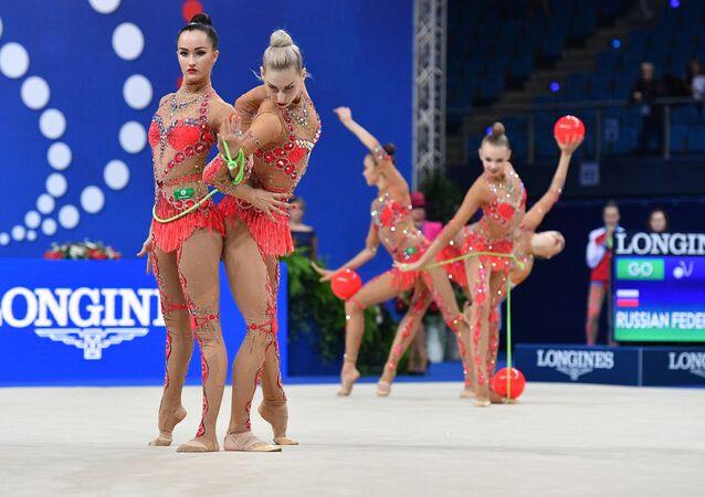 أفضل صور وكالة سبوتنيك من بطولة الجمباز الإيقاعي في بيزارو، إيطاليا - المنتخب الروسي وعرض الجمباز الإيقاعي مع ثلاث كرات وحبلي القفز
