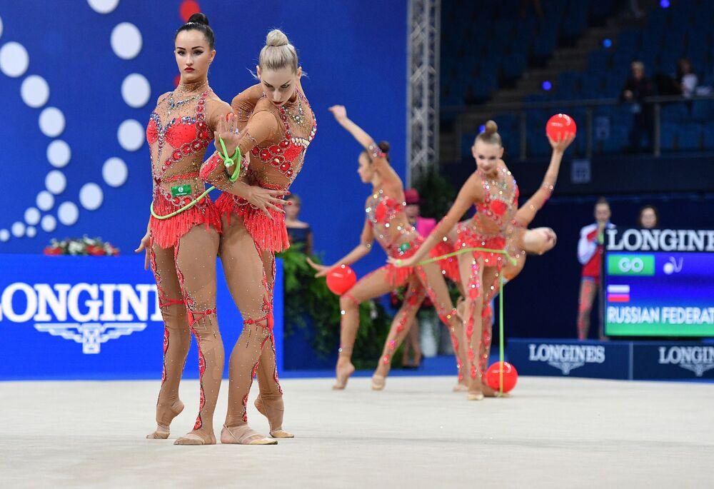 أفضل صور وكالة سبوتنيك من بطولة الجمباز الإيقاعي في بيزارو، إيطاليا - المنتخب الروسي وعرض الجمباز الإيقاعي مع ثلاث كرات و حبلي القفز