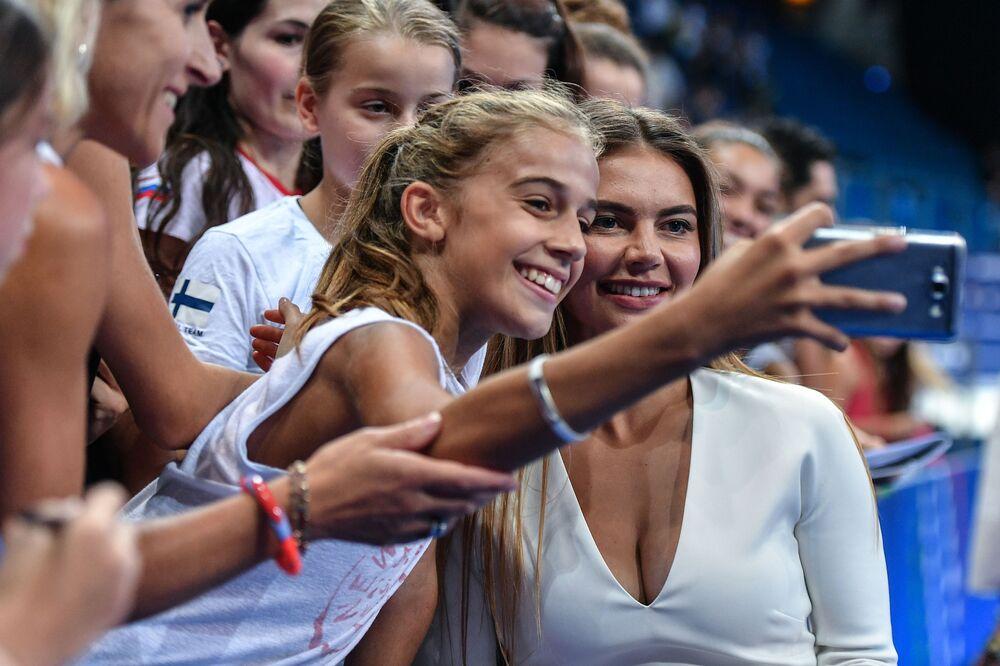 أفضل صور وكالة سبوتنيك من بطولة الجمباز الإيقاعي في بيزارو، إيطاليا - جمهور يلتقط صورة سيلفي مع الرياضية الروسية الأولمبية ألينا كابايفا