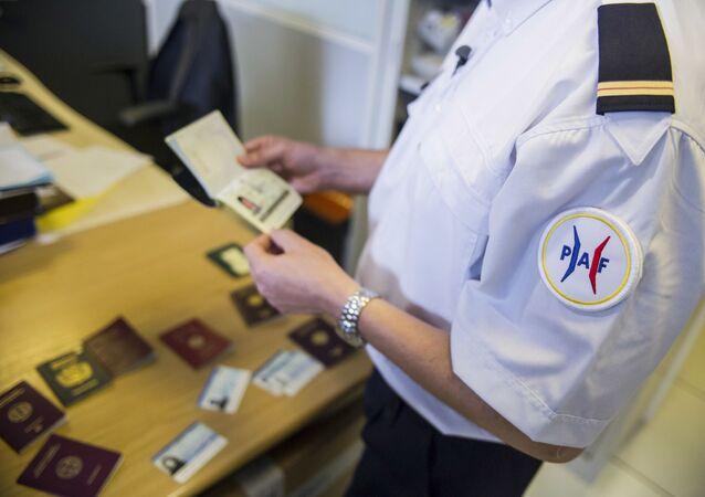شرطي فرنسي يتفقد جوازات السفر المزورة