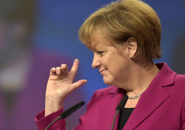 German Chancellor and chairwoman of the German Christian Democrats, CDU, Angela Merkel, points with her fingers during a visit to the convention venue prior to the 27. party convention in Cologne, Germany, Monday, Dec. 8, 2014.