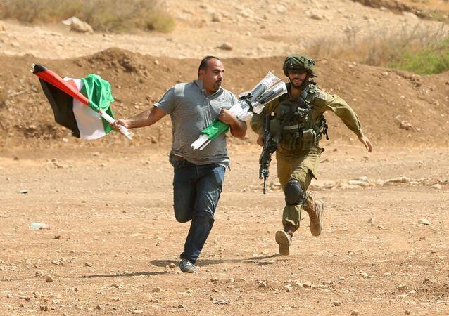 جندي إسرائيلي يركض خلف متظاهر فلسطيني خلال الاشتباكات دارت بين المتظاهرين والجيش الإسرائيلي في بلدة طوباس بالضفة الغربية، فلسطين 27 سبتمبر/ أيلول 2017