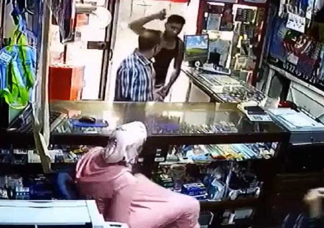 لص يقتحم محل تجاري ويهدد فتاتين بالسيف (فيديو)