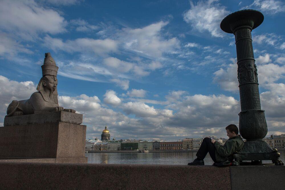شاب يرسم على ضفة أونيفرسيتيتسكايا في مدينة سان بطرسبورغ، روسيا