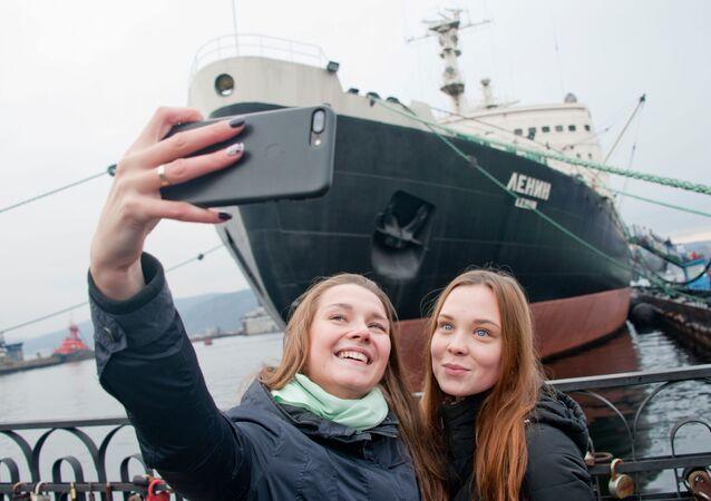 فتاتان تلتقطان صورة سيلفي على خلفية متحف كاسحة الجليد لينين في مورمانسك، روسيا