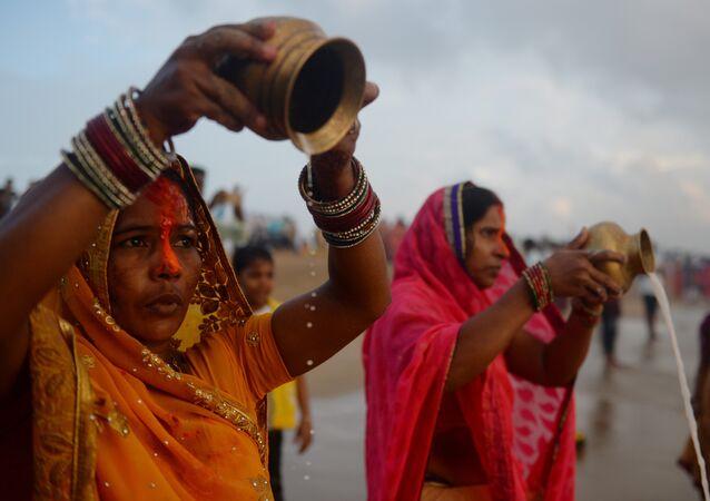 هنديات يتعبدون لسلة مهملات