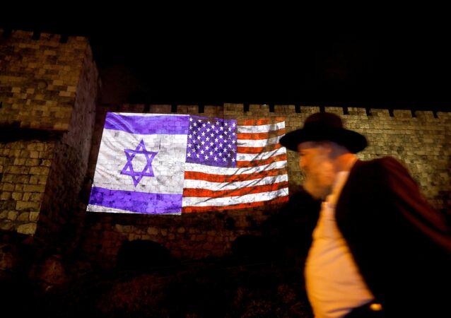 رجل يسير علعى خلفية إنعكاس العلمين الإسرائيلي والأمريكي على سور بمدينة القدس القديمة، 6 ديسمبر/ كانون الأول 2017