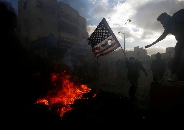 متظاهرون فلسطينيون يحرقون العلم الأمريكي احتجاجا على قرار الرئيس دونالد ترامب بشأن القدس، بالقرب من مستوطنة إسرائيلية في بيت إيل، الضفة الغربية، 7 ديسمبر/ كانون الأول 2017