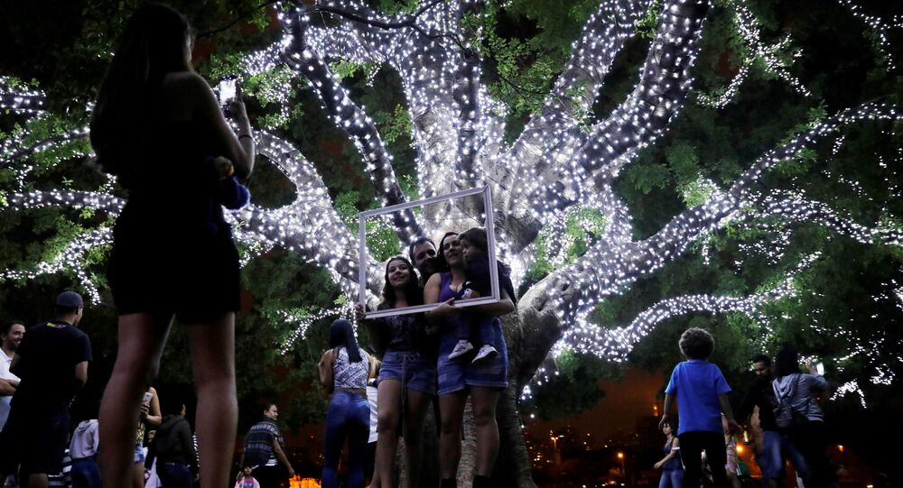 عائلة تلتقط صورة داخل إطار على خلفية شجرة الكريسماس في سان باولو، البرازيل 3 ديسمبر/ كانون الأول 2017