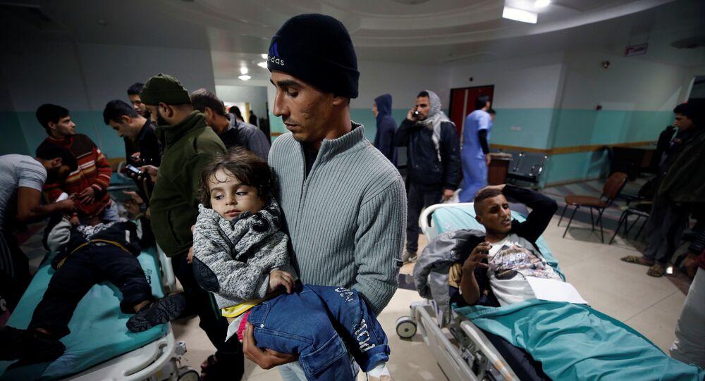 فلسطيني يحمل ابنته الجريحة وهي تنتظر تلقي العلاج بعد غارات جوية إسرائيلية قريبة من مستشفى في شمال قطاع غزة