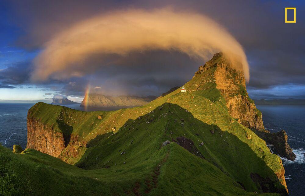 مسابقة ناشيونال جيوغرافيك للطبيعة لعام 2017 - المصور ويسيش كروسزينسكي، صورة بعنوان غروب ينير المنارة في جزر فارو