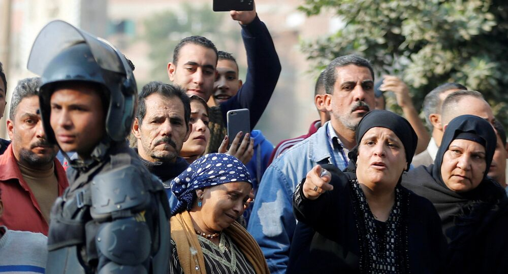 الناس بالقرب من موقع الهجوم على كنيسة مار مينا في منطقة حلوان على مشارف القاهرة