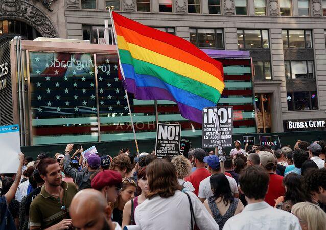 علم قوس قزح يرفرف بينما يحتج الناس على حظر الرئيس الأمريكي دونالد ترامب لأشخاص متحولين جنسيا من الخدمة في الجيش الأمريكي في نيويورك
