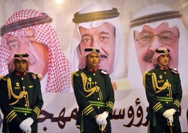 الحرس الملكي السعودي وفي الخلفية صورة للملك عبد الله بن عبد العزيز والملك سلمان بن عبد العزيز والأمير مقرن بن عبد العزيز