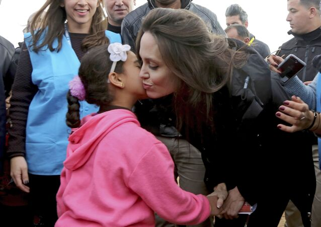 سفيرة الأمم المتحدة للنوايا الحسنة، أنجولينا جولي تقبل طفلة لاجئة سورية، خلال زيارتها لمخيم الزعتري للاجئين السوريين في المفرق شمال الأردن