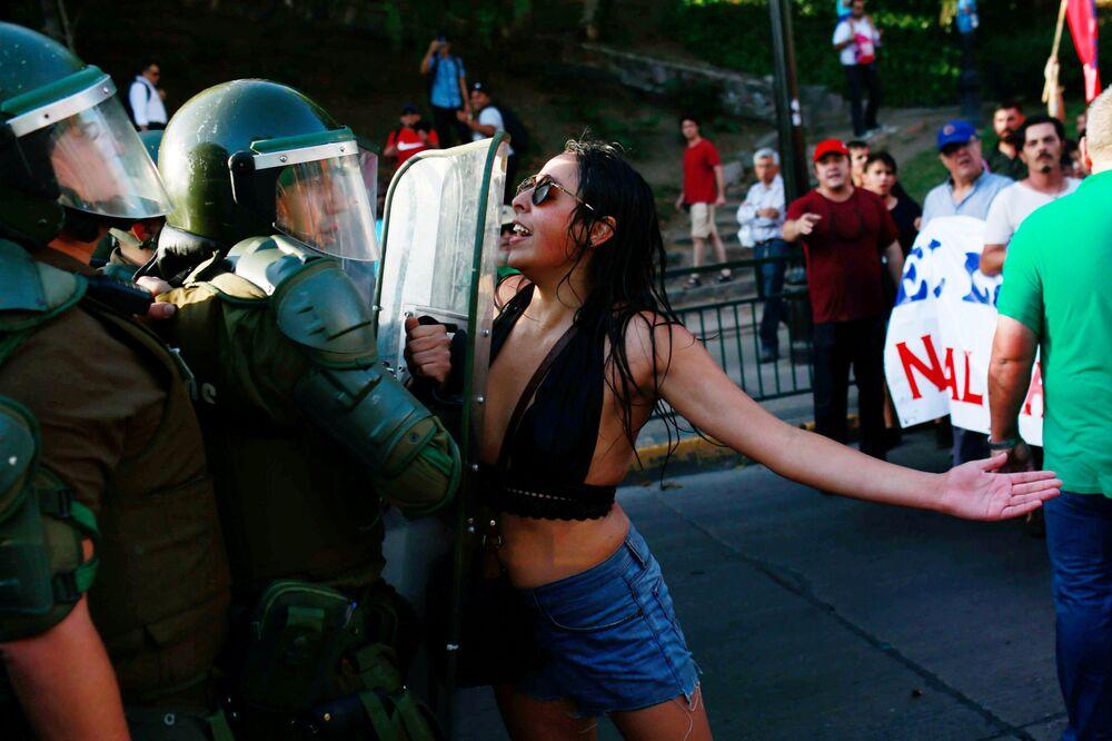 متظاهرة تصرخ على شرطي خلال مظاهرة في سانتياغو، تشيلي 29 يناير/ كانون الثاني 2018