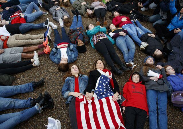 طلبة يستلقون أمام البيت الأبيض في العاصمة الأمريكية واشنطن الاثنين 19 فبراير/شباط 2018 لمطالبة الحكومة بإجراء تغييرات في قوانين الأسلحة بعد حادث هجوم مدرسة مارجوري ستونيمان دوغلاس