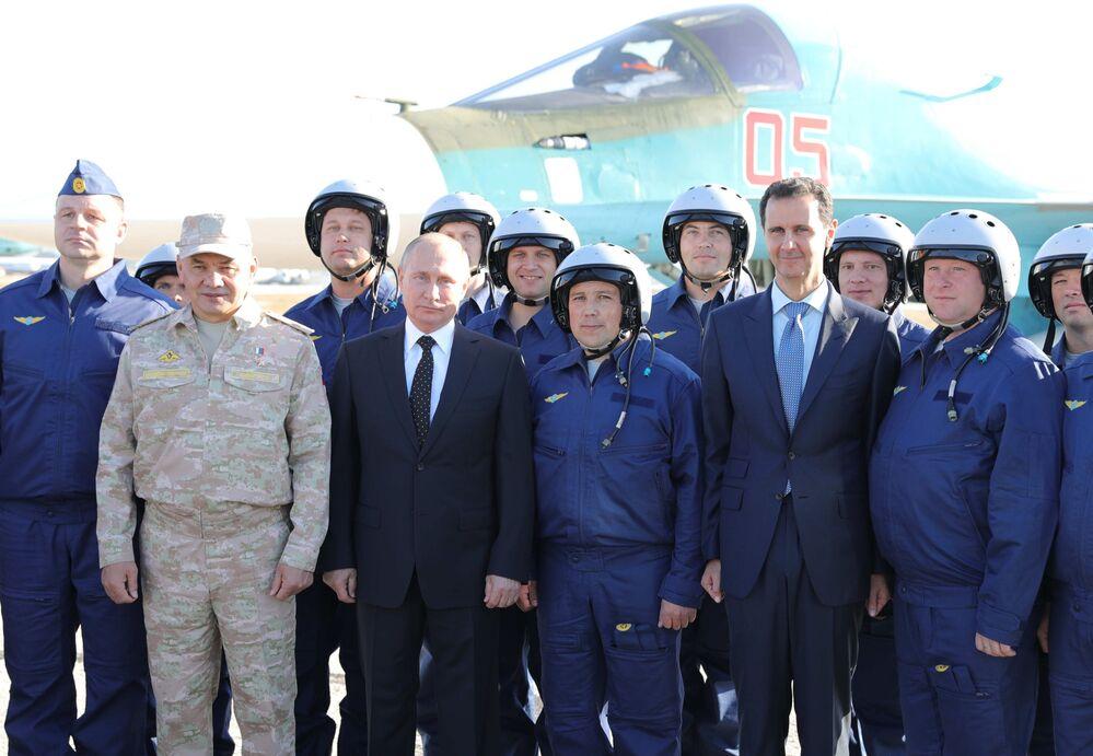 الرئيس فلاديمير بوتين والرئيس السوري بشار الأسد يلتقطون صورة جماعية في القاعدة الجوية السورية حميميم، 11 ديسمبر/ كانون الأول 2017