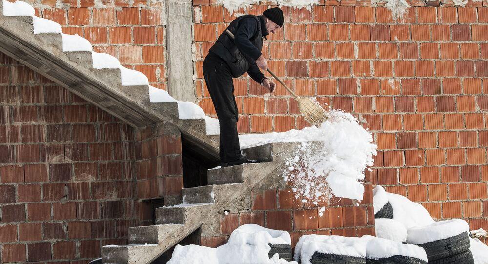 رجل يقوم بتنظيف الثلج على درج المنزل في قرية مرامور، بريشتينا، سيبيريا 27 فبراير/ شباط 2018