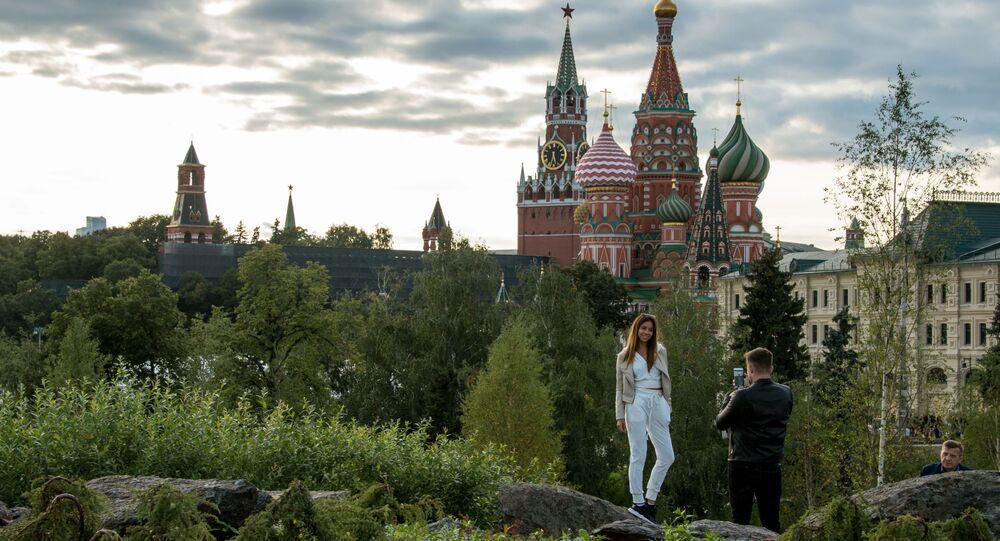 زائران يلتقطان الصور في حديقة زاريادي على خلفية الكرملين والساحة الحمراء في موسكو