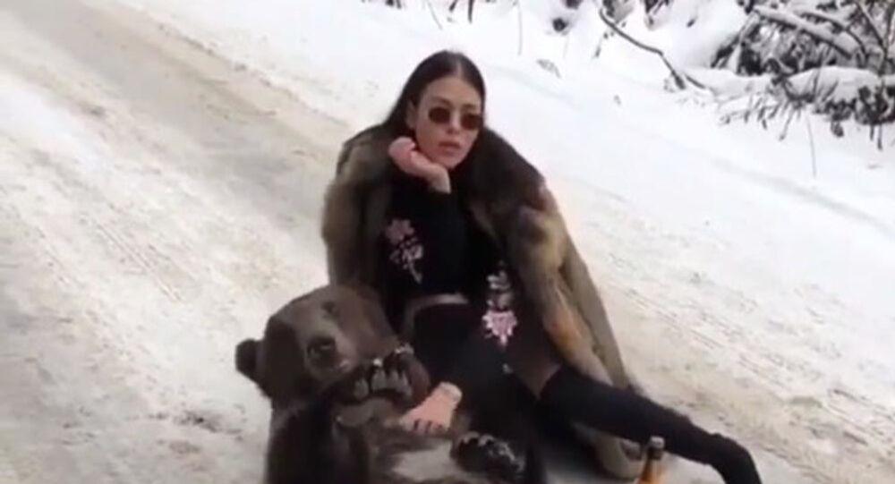 فتاة في معطف من الفرو، على طريق مغطى بالثلج مع زجاجة من الشمبانيا ودب حي