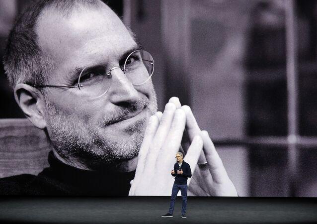 رئيس شركة أبل الأمريكية تيم كوك وفي الخلفية صورة لمؤسس الشركة الراحل ستيف جوبز