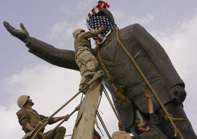 مجند أمريكي يضع علم الولايات المتحدة على رأس تمثال صدام حسين في عام 2003 في بغداد