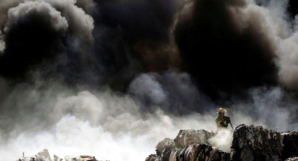 رجل إطفاء يخمد حريق في كومة من الإطارات القديمة في مركز إعادة التدوير في سيوداد خواريز، المكسيك 2 مايو/ أيار  2018