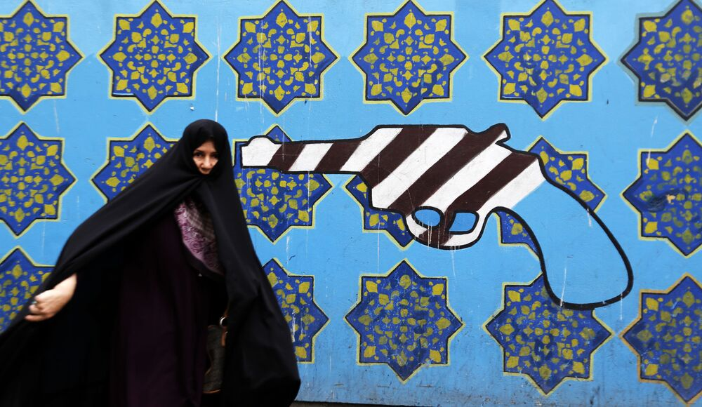 امرأة إيرانية على خلفية رسم غرافيتي على جدار المبنى السابق السفارة الأمريكية في طهران، إيران 8 مايو/ أيار 2018