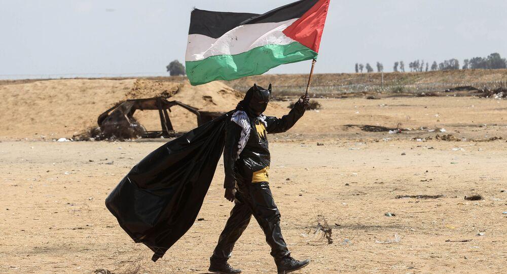 شاب فلسطيني يحمل العلم الفلسطيني، مرتديا زي ارجل الوطواط، خلال فعاليات مسيرات العودة في شرق خانيونس، على الحدود بين قطاع غزة وإسرائيل، 9 مايو/ أيار 2018