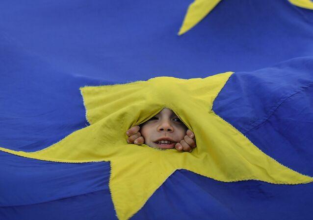 صبي يظهر من خلال ثقب في علم الاتحاد الأوروبي أثناء مسيرة في بوخارست، رومانيا، 12 مايو/ أيار 2018