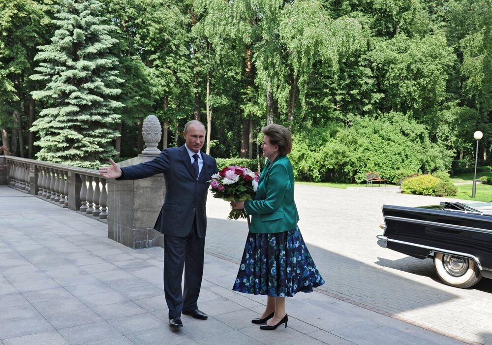 الرئيس الروسي فلاديمير بوتين يهدي باقة ورود لفالينتينا تيريشكوفا، أول رائدة فضاء وبطلة الاتحاد السوفيتي في مقره الرئاسي في نوفو-أوغاريفو