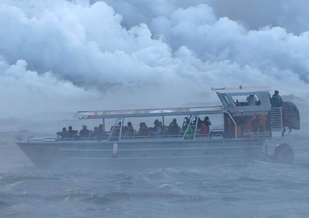 الناس يشاهدون من قارب سياحي بينما تتدفق الحمم البركانية في المحيط الهادئ في منطقة كابوهو، أثناء ثوران بركان كيلاويا في هاواي، الولايات المتحدة 4 يونيو/ حزيران 2018