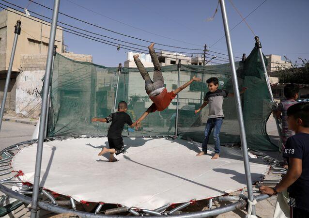 أطفال يلعبون الترامبولين في العاصمة الأردنية عمان
