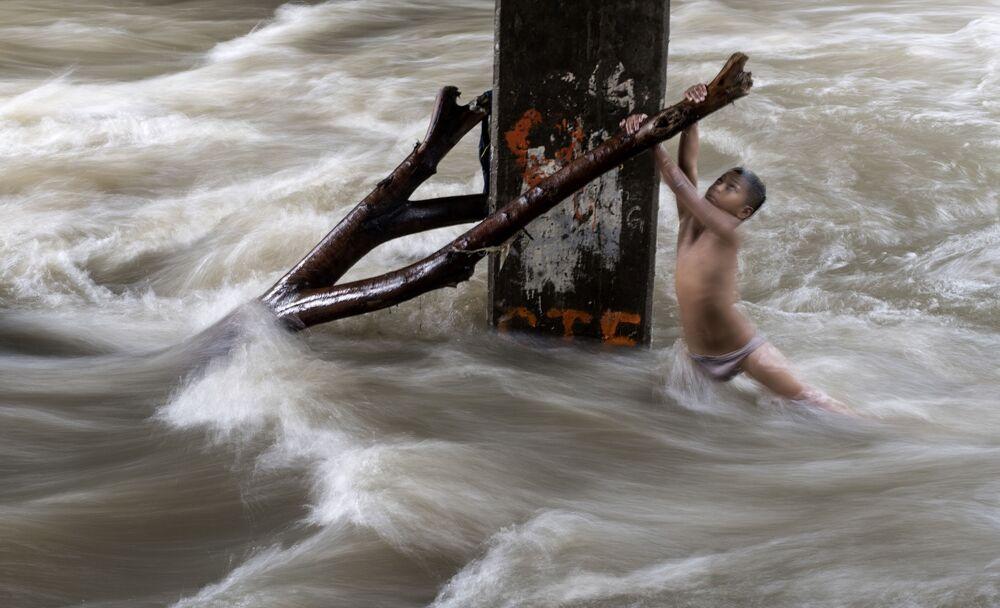 صبي يمسك بغصن شجرة خشية الانجرار في نهر فاض بسبب الأمطار الغزيرة في مانيلا، الفلبين 11 يونيو/ حزيران 2018