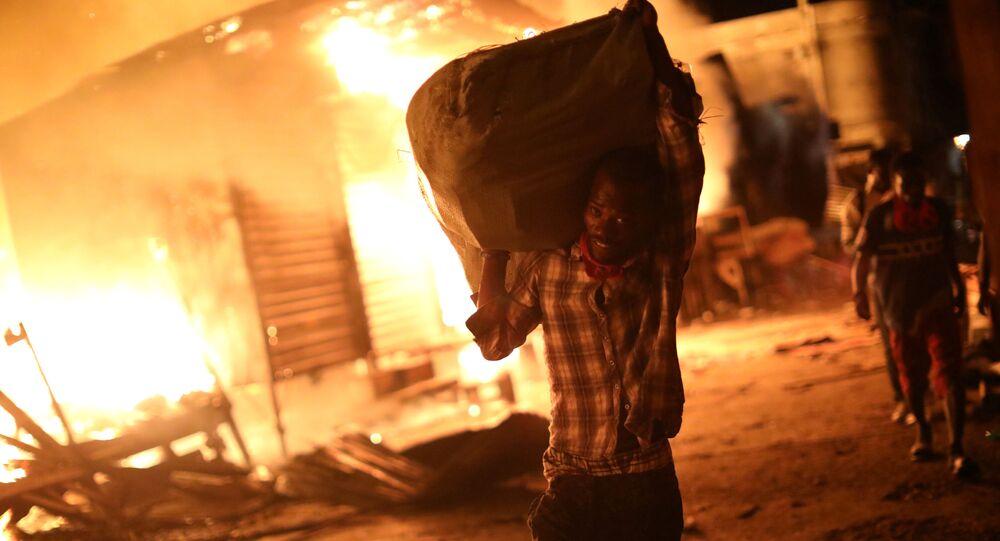رجل يحمل حقيبة من البضائع أثناء حريق في السوق في بورت-أو-برنس، هايتي 12 يونيو/ حزيران 2018