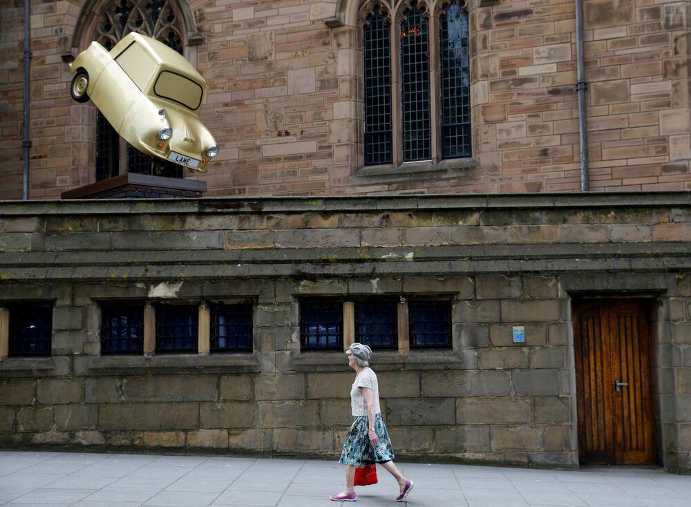 امرأة تسير بالقرب من عرض فني Gold Lamé، للفنان توني هيتون في ليفربول، بريطانيا 12 يونيو/ حزيران 2018