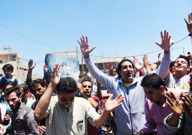 مواطنون من مدينة درعا السورية يحتفلون بدخول الجيش السوري بعد تحرير بلدتهم من الإرهابيين