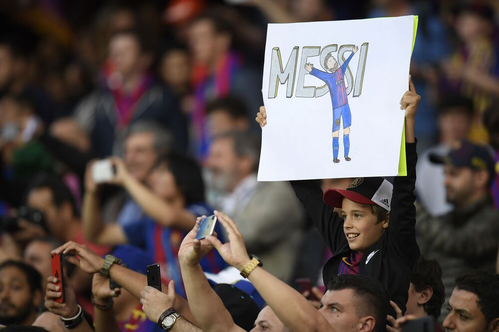 صبي يحمل لافتة للاعب فريق برشلونة والمنتخب الأرجنتيني ليونيل ميسي