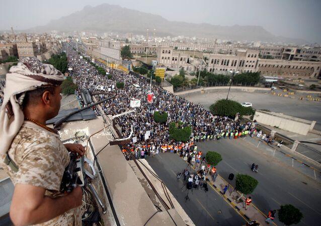 أحد عناصر انصار الله  يقوم بتأمين مظاهرة تندد بالقصف على الحديدة من قبل التحالف العربي