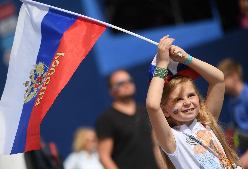 مشجعة صغيرة ترفع علم روسيا خلال تجشيعها للمنتخب الروسي في مباراة مرحلة المجموعة روسيا وأورغواي، 2018