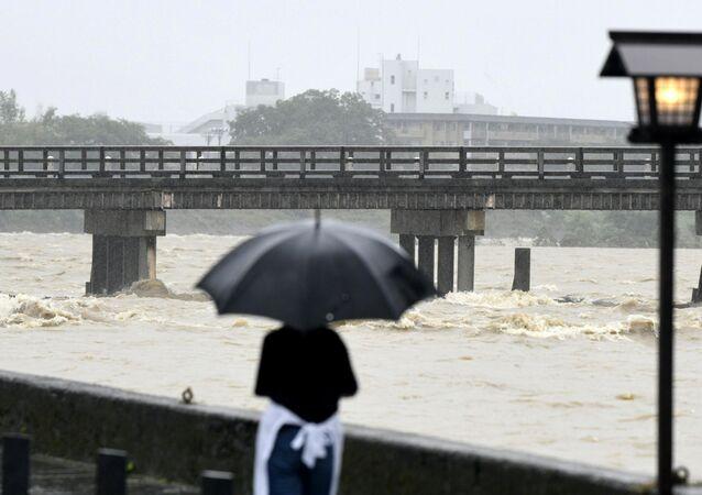 أحد السكان المحليين يشاهد جسر توجتسوا وتدفق نهر كاتسورا أسفله بسبب المطر الغزير في كيوتو في اليابان، 6 يوليو/تموز 2018