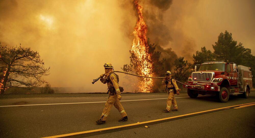 رجال الإطفاء على خلفية ألسنة اللهب على الطريق السريع بالقرب من كليرليك أوكز، كاليفورنيا، الولايات المتحدة 1 يوليو/ تموز 2018