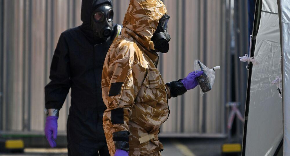 محققون في أقنعة واقية من الغاز، أثناء التحقيق في أسباب تسمم الرجال والنساء في إيسمبري، المملكة البريطانية المتحدة 6 يوليو/ تموز 2018
