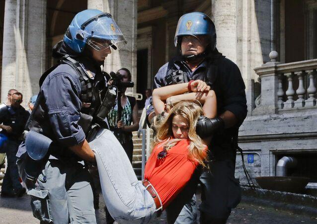 أفراد الشرطة الإيطالية يمسكون بأحد المتظاهرين خارج مبنى وزارة النقل ، خلال احتجاجات ضد سياسة الحكومة حول الهجرة في روما، إيطاليا 11 يوليو/ تموز 2018