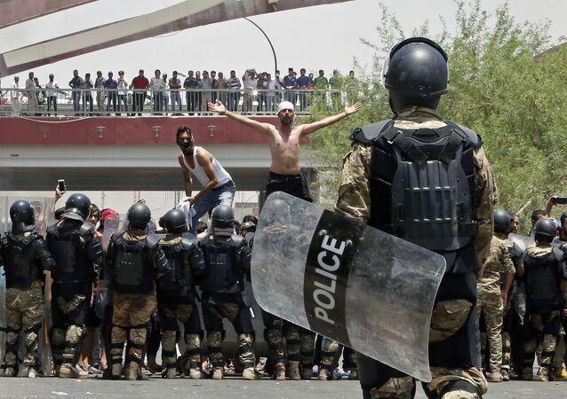 شرطة مكافحة الشغب العراقية تمنع المحتجين من اقتحام مبنى مجلس المحافظة خلال مظاهرة في البصرة، على بعد 550 كم جنوب شرق بغداد، العراق  15 يوليو/ تموز2018