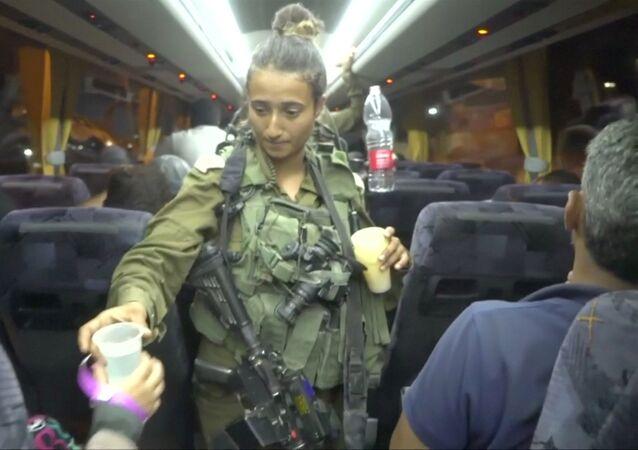 جندية إسرائيلية توزع الماء على أعضاء الخوذ البيضاء في الباصات عند خروجهم من سوريا