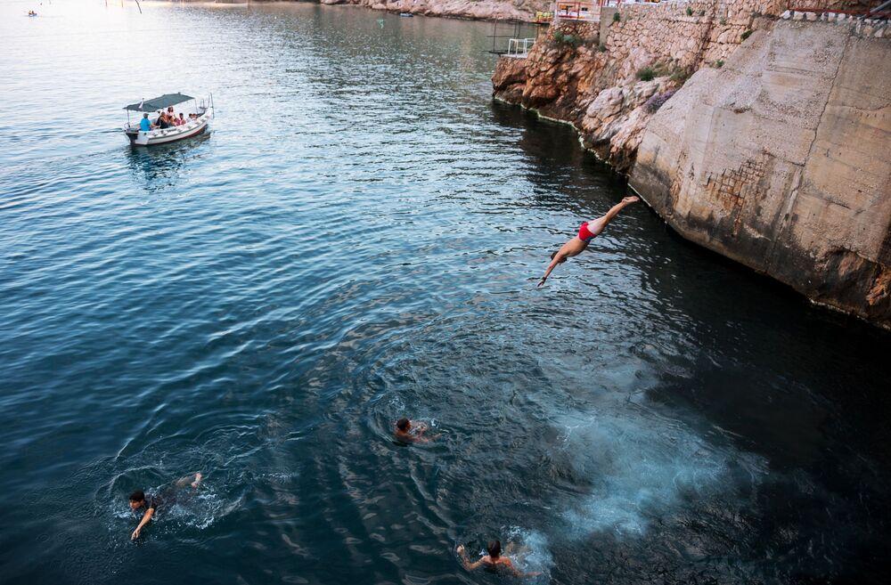 أطفال يقفزون إلى مياه البحر في بالاكلافا، القرم